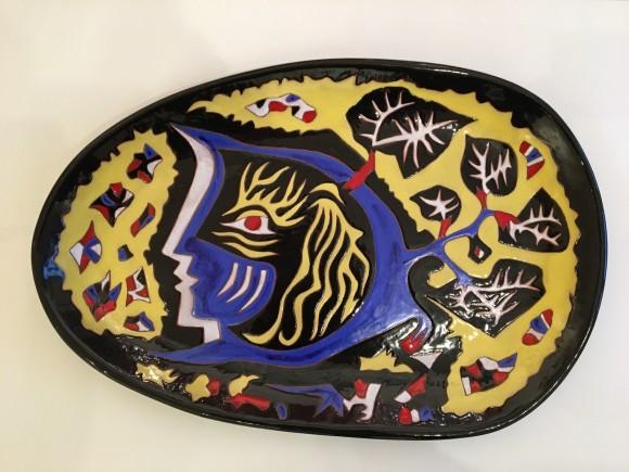 Grand plat à motif d'un visage stylisé bleu
